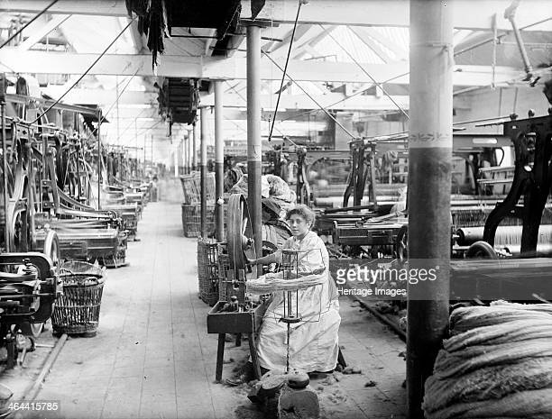 Early Blanket Factory Witney Oxfordshire 1898 Interior of the loom shop showing a young woman winding bobbins on a wheel The mill machinery can be...