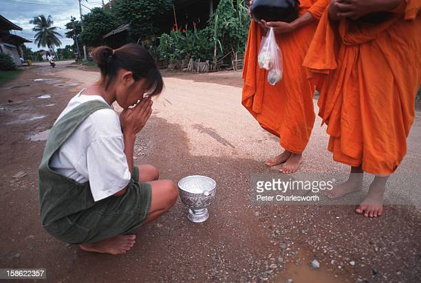 SUKHOTHAI SUKHOTHAI THAILAND Early in the morning a young woman kneels at the feet of two monks as she receives a blessing having given alms to the...