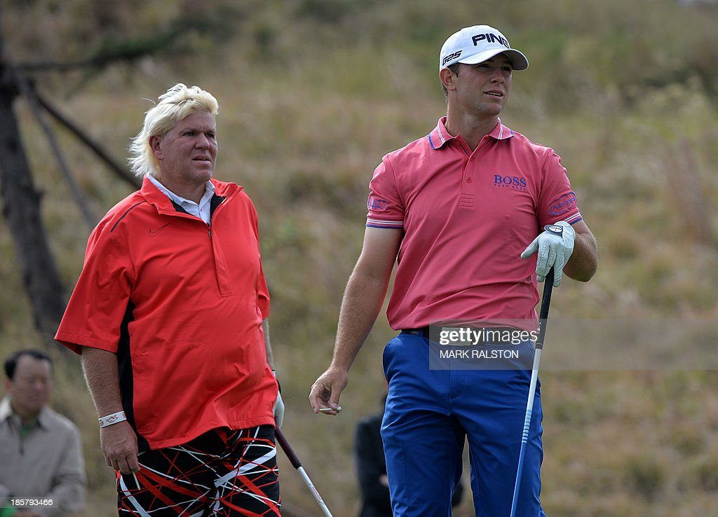 Early leader Luke Guthrie of the US (R) watches his tee shot beside John Daly of the US at the 8th hole during day two of the BMW Shanghai Masters golf tournament at the Lake Malaren Golf Club in Shanghai on October 25, 2013. The 7 million USD event is being held for the second time at the Lake Malaren Golf Club. AFP PHOTO/Mark RALSTON