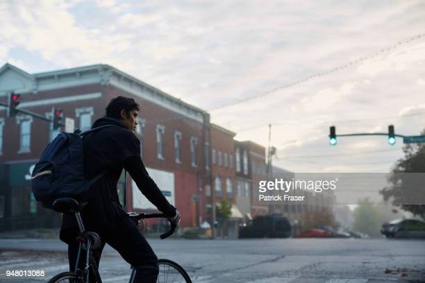 Early morning commuter waits on bicycle at stoplight in small town