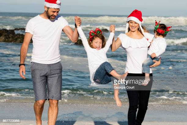 early morning family fun summer christmas on the beach - beach christmas stock pictures, royalty-free photos & images