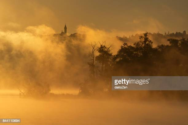 Early morning fog on Lake Ammersee with Andechs monastery in the distance, Upper Bavaria, Germany