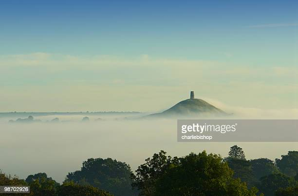 early morning fog rolling in over glastonbury tor - glastonbury england stock pictures, royalty-free photos & images