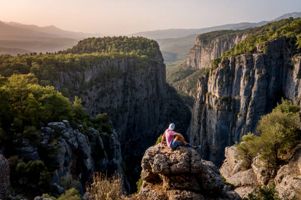 Early morning, just after sunrise. Tazi Canyon (Bilgelik Vadisi) in Manavgat, Antalya, Turkey. A man sits on the edge of a cliff against the backdrop of a gorge