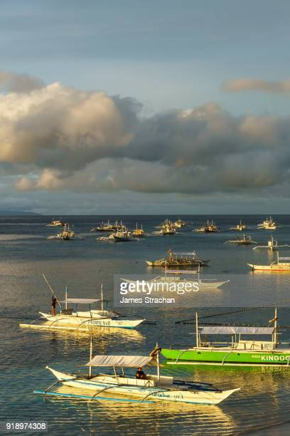 Early morning light on the bangkas (outrigger canoes)  berthed by Panglao Beach, Bohol Island, Philippines