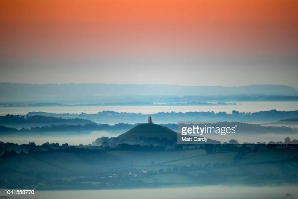 Early morning mist lingers below Glastonbury Tor as the sun rises viewed from the Mendips near Wells on September 27 2018 in Somerset England After...