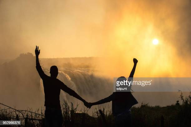 early morning silhouette of couple at victoria falls arms raised - zimbabwe stock pictures, royalty-free photos & images
