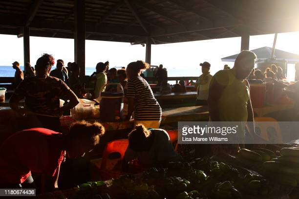 Early morning stall holders and shoppers are seen at the Honiara Central Markets as performers from the 'Solomon Islands Cultural Group' prepare to...