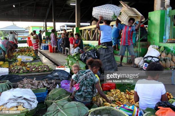 Early morning stall holders prepare produce at the Honiara Central Markets as performers from the 'Solomon Islands Cultural Group' prepare to for the...
