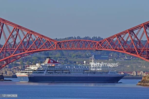 Early morning sun catches the Fred Olsen Cruise Lines ship Balmoral as she passes under the Forth Bridge en route to the Port of Rosyth on May 06 in...