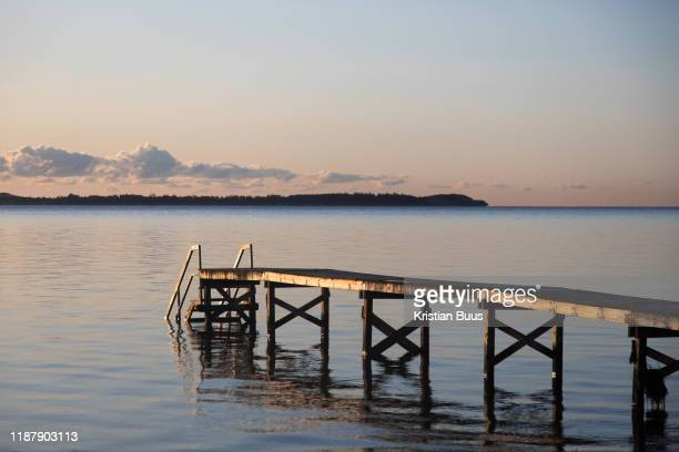 Early morning sun shines on a wooden pier Oct 29th 2019 Skæring Denmark The sea is calm on an early autumn morning The sea is blue and the wooden...