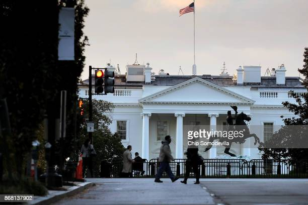 Early morning sunlight hits the US flag flying over the White House October 30 2017 in Washington DC Former Trump campaign manager Paul Manafort and...