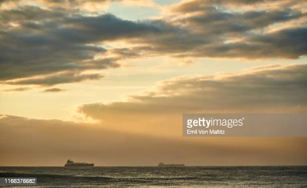 early morning sunrise with freight liner ships on the horizon. full colour image. indian ocean, durban, kwazulu-natal, south africa - インド洋 ストックフォトと画像