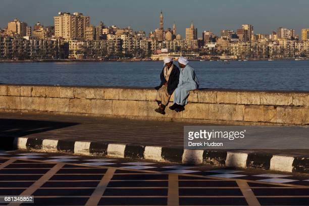 Early morning view of a pair of men as they sit and talk on the seawall of the Eastern Harbor with the city skyline behind them Alexandria Egypt...