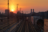Early morning view of railroad tracks leading to Munich Central Station with Bell Towers of Frauenkirche (Church of Our Lady), Munich, Bavaria, Germany