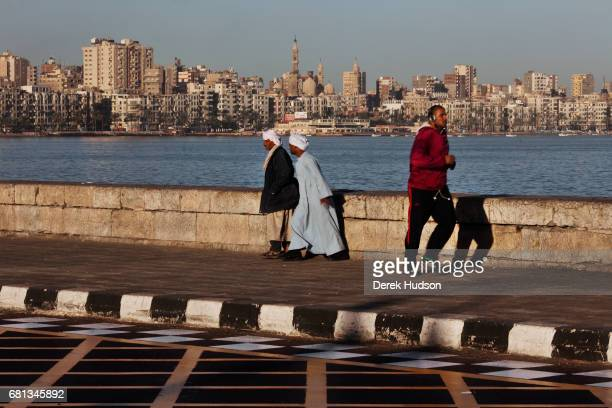 Early morning view two pedestrians and a jogger at the seawall of the Eastern Harbor with the city skyline behind them Alexandria Egypt December 5...