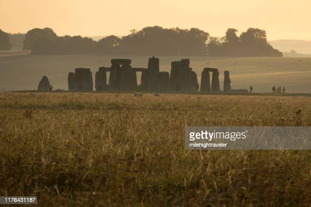 early morning visitors explore stonehenge monument salisbury plain wiltshire england - milehightraveler stock pictures, royalty-free photos & images
