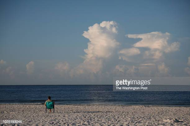 August 26: Early morning visitors sit on Siesta Beach on August 26, 2018 in Siesta Key, Florida. Florida Governor Rick Scott declared a state of...
