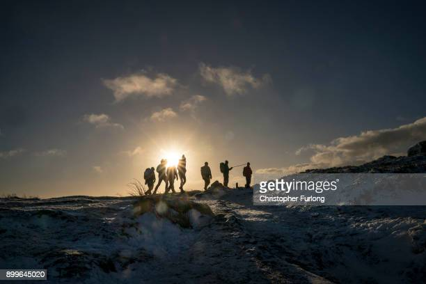 Early morning walkers ascend Higger Tor as snow covers the tops of the hills in the Peak District on December 28, 2017 in Sheffield, England....