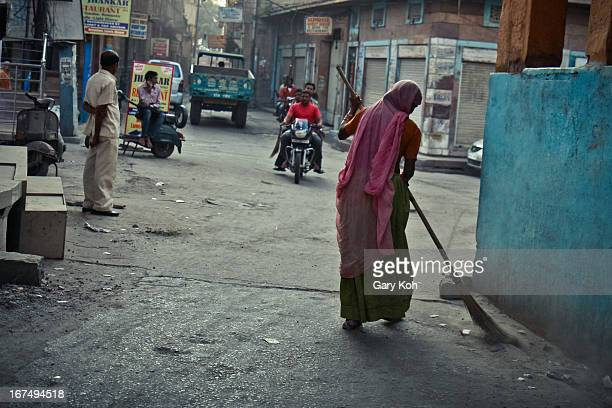 "Early one morning in Jodhpur - India's famous ""blue city"" - a woman goes to work sweeping its dusty streets. Rajasthan, India."
