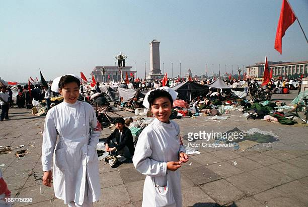 Early one morning two nurses walk through Tiananmen Square Prodemocracy demonstrators and protestors filled the square for weeks prior to the final...