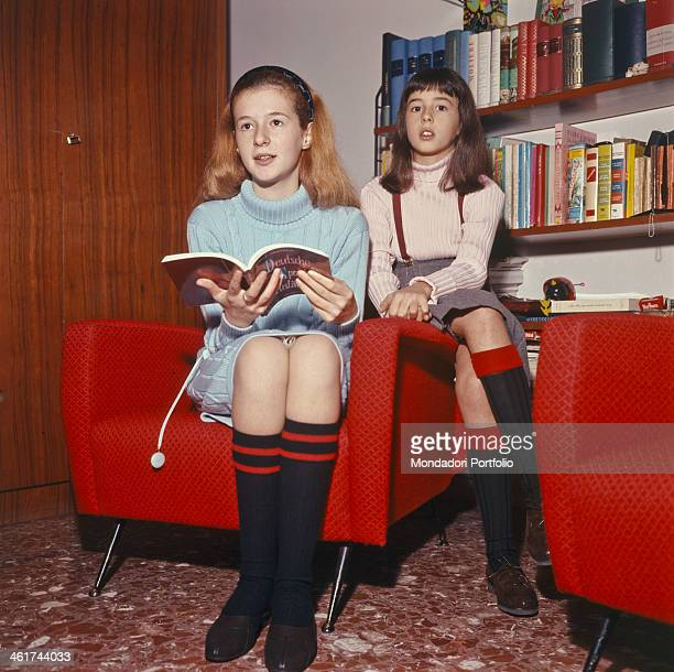 Early shoot of the sisters Loretta busy leafing through a book and Daniela Goggi wearing dolcevita kneelength socks and wrinkled skirts sitting in an...