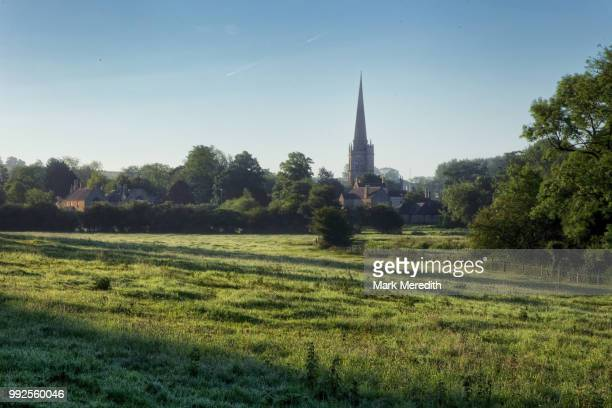 early summer morning shadows sweep a field in burford in the cotswolds - 尖り屋根 ストックフォトと画像