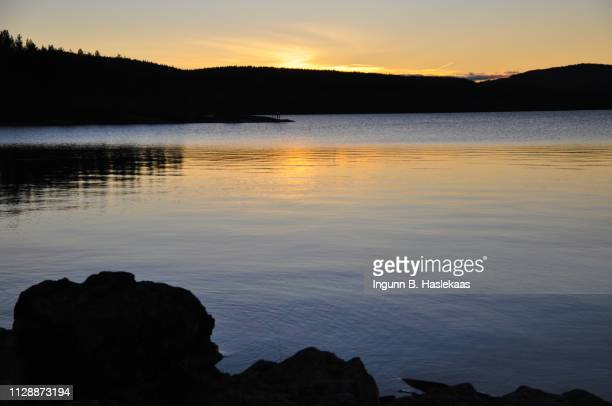 early sunset on a cold day in late autumn by lake follsjo. reflection of the setting sun in the water. - hill range stock pictures, royalty-free photos & images