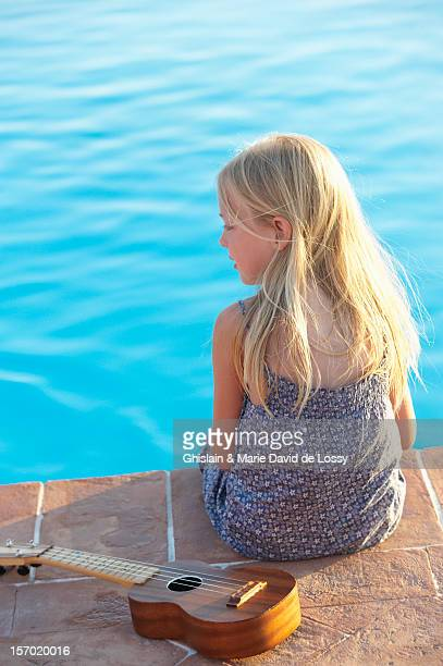 Early teen girl sitting by the pool with ukulele
