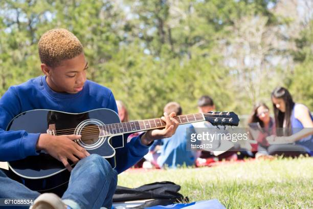 Early teenage boy playing guitar in park with friends.