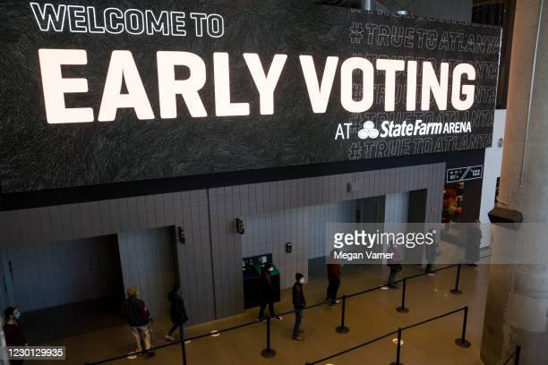 Early voters stand in line at the State Farm Arena on December 14, 2020 in Atlanta, Georgia. Early voting started today in Georgia for the runoff...