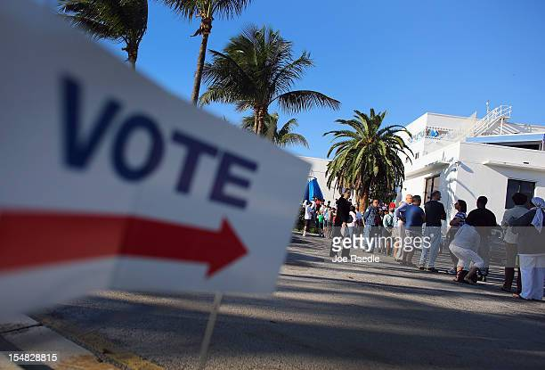 Early voters wait in line to vote in the presidential election on the first day of early voting at a polling station setup at the City of Miami City...