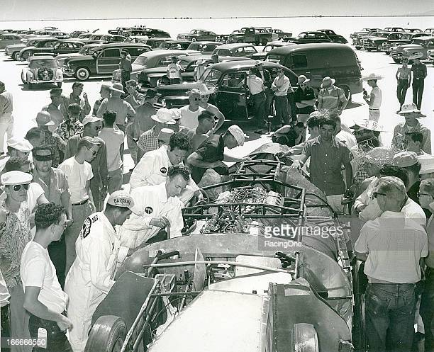 Spectators look on as crewmembers work on a car before making a speed trial run at the Bonneville Salt Flats