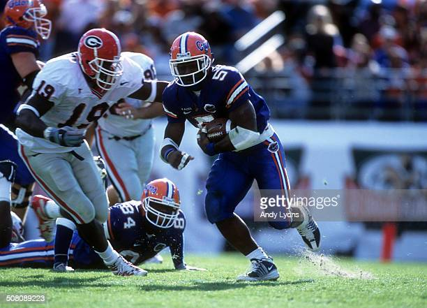 Earnest Graham of the Florida Gators runs with the ball as Charles Grant of the Georgia Bulldogs goes for the tackle on October 27, 2001 at Alltel...