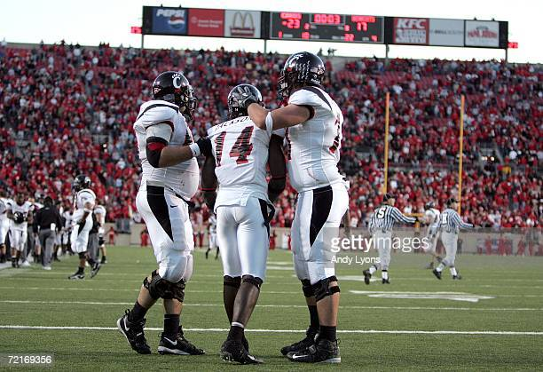 Earnest Jackson of the Cincinnati Bearcats is comforted by Jeff Reinstatler and Jeffrey Linkenbach in the endzone after Jackson was unable to catch a...