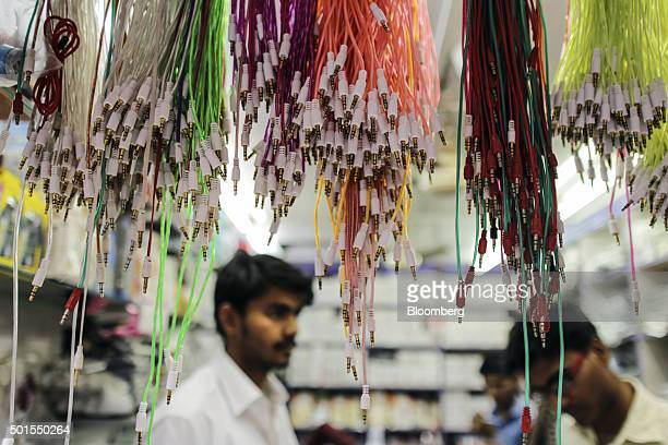 Earphone cables hang on display inside a mobile phone store in the Relief Road area of Ahmadabad Gujarat India on Monday Dec 14 2015 India's rupee is...