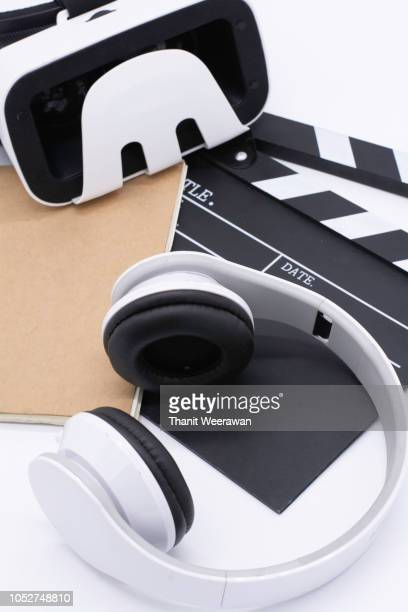Earphone, Movie clapper board, note pad and with VR player on white background