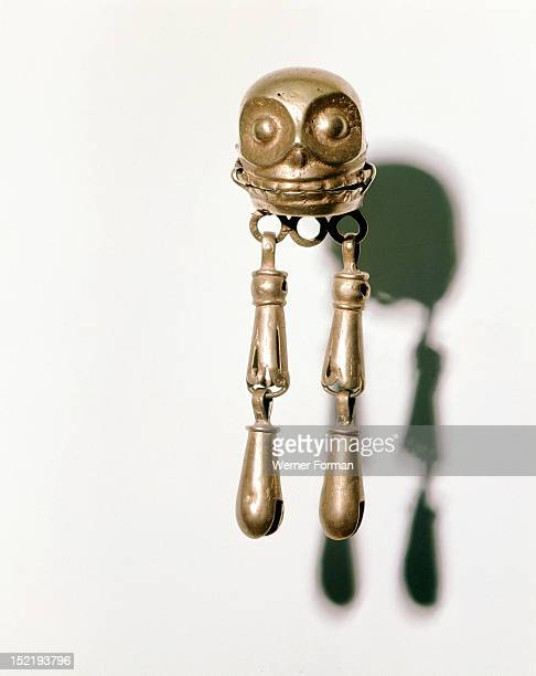 Earring composed of a gold skull from which hang tiny bells The greatest traditions of craftmanship in Ancient Mexico were among the Mixtecs who...