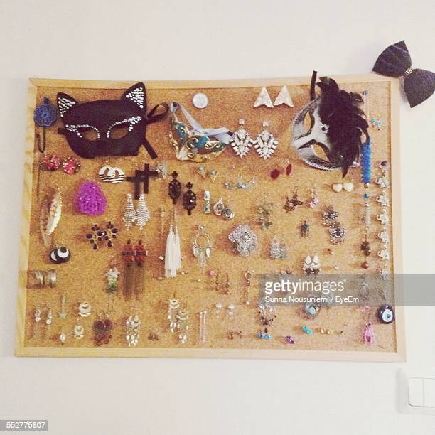 Earrings And Masks Hanging On Wall