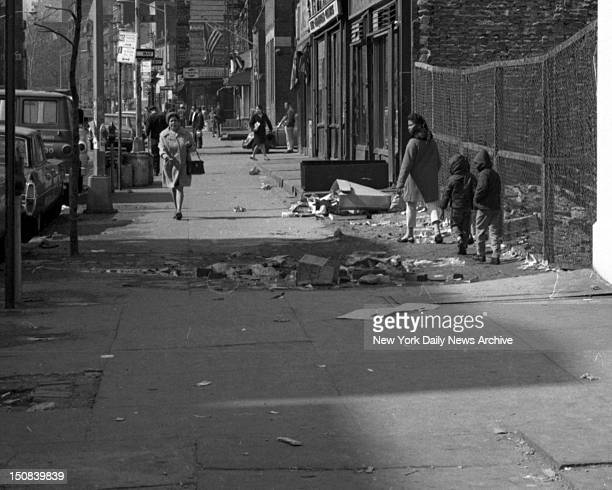 Earth Day, Pedestrians avoid litter as they make way along Avenue C between Fourth and Fifth Sts.