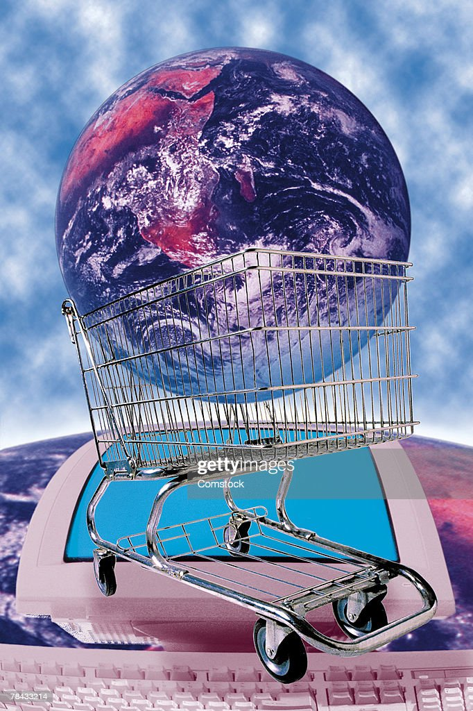 Earth in shopping cart on top of image of computer on Earth : Stockfoto