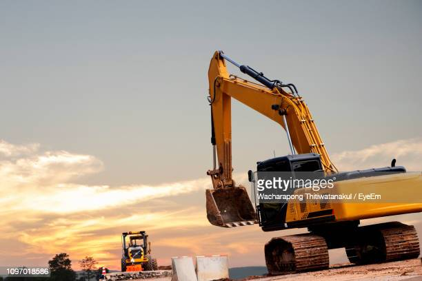 earth mover at construction site against sky during sunset - bulldozer stock pictures, royalty-free photos & images
