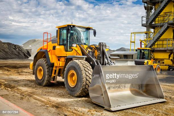 motor de terra em frente a fábrica de cimento - escavadora mecânica - fotografias e filmes do acervo