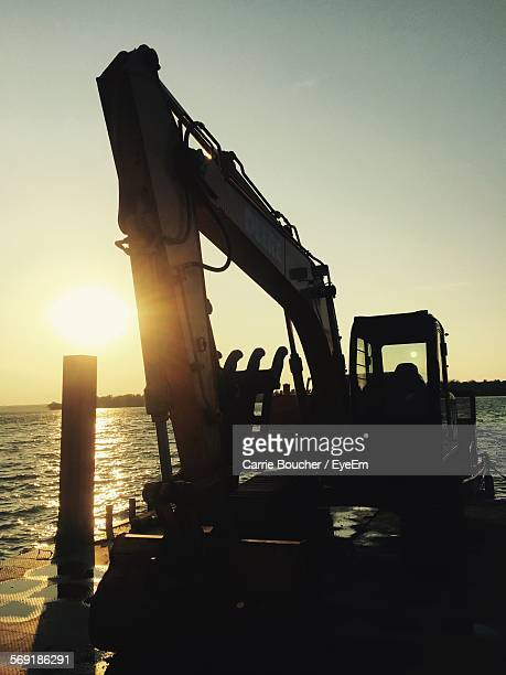 Earth mover in front of river against sky during sunset