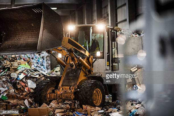 Earth mover in the garbage dump with female driver