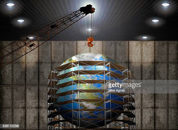 earth with crane and scaffolding - mike agliolo stock pictures, royalty-free photos & images