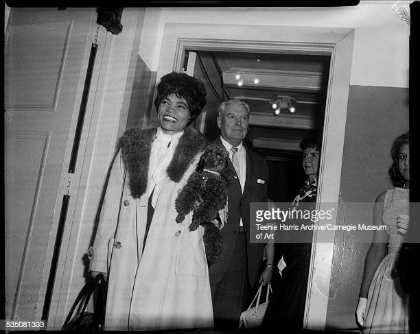 Eartha Kitt carrying poodle and David McDonald standing in hallway of Syria Mosque for Maurice Stokes benefit Pittsburgh Pennsylvania June 1961