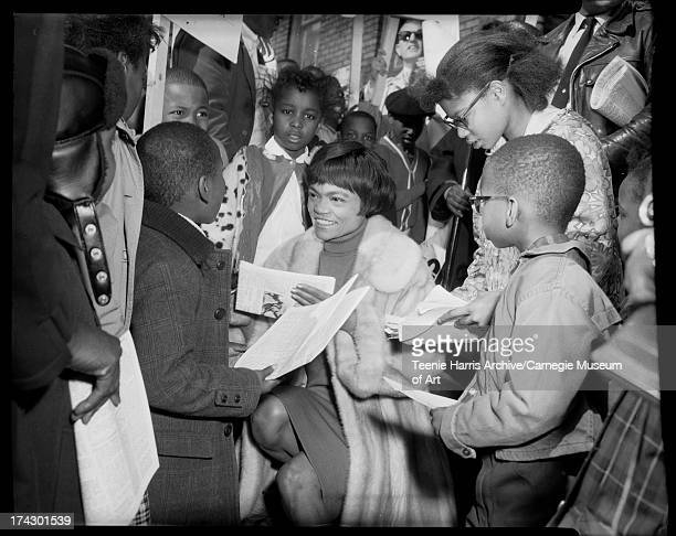 Eartha Kitt signing autographs and surrounded by children including Mignon Threatt on right for Citizens Committee on Hill District Renewal program...