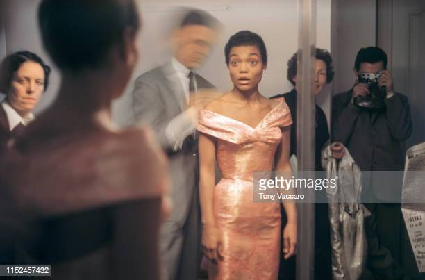 Eartha Kitt standing in front of a mirror looking at her self as she is getting dressed by Givenchy. She is in shock seeing her reflection in her...