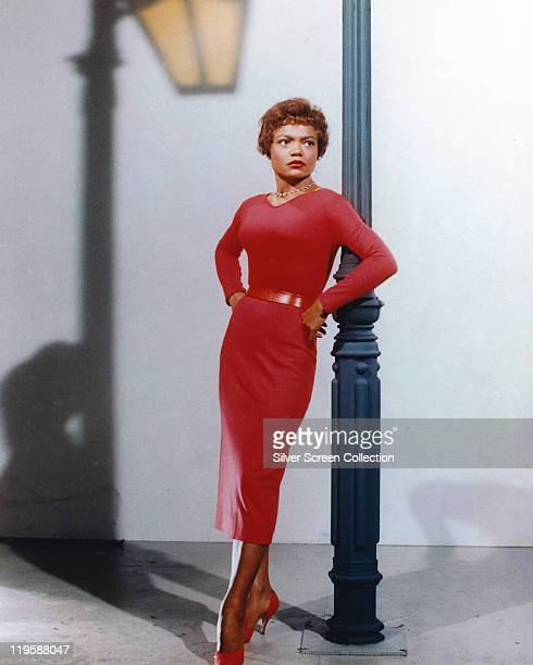 Eartha Kitt US actress and singer wearing a red dress with a red belt leaning against a lamppost in a studio portrait the shadow of the lamppost is...